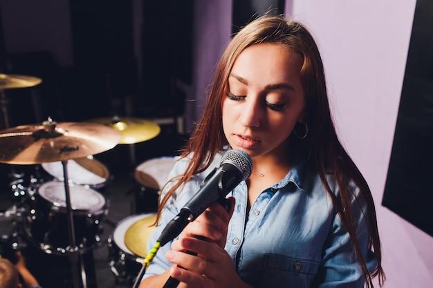 Cerca de un cantante grabando una pista en un estudio.