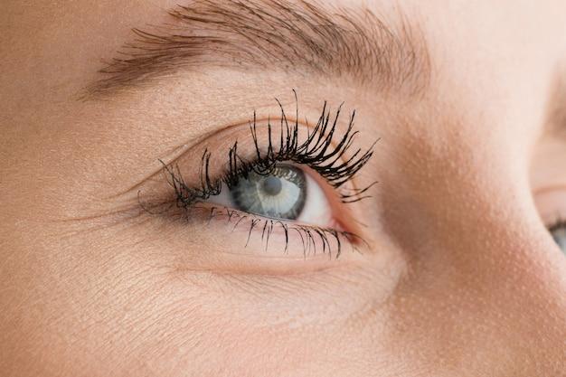 Cerca de la cara de la hermosa joven caucásica, se centran en los ojos. las emociones humanas, la expresión facial, la cosmetología, el cuerpo y el concepto de cuidado de la piel.