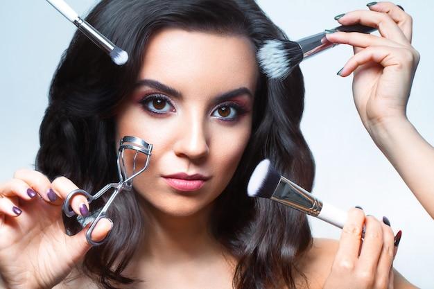 Cerca de la cara de una mujer joven con todo tipo de herramientas de maquillaje: pincel, lápiz labial, etc.
