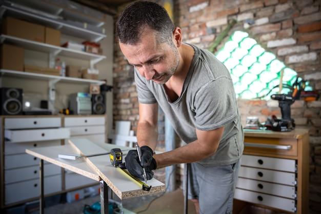 Cerca de carpintero enfocado sosteniendo una regla y un lápiz mientras hace marcas en la madera en la mesa del taller.