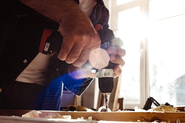 Cerca de un carpintero perforando un agujero en la madera