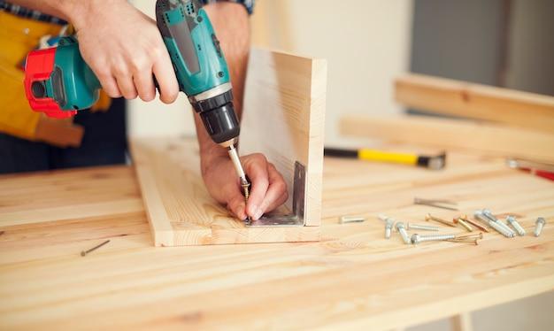 Cerca de carpintero trabajando con taladro