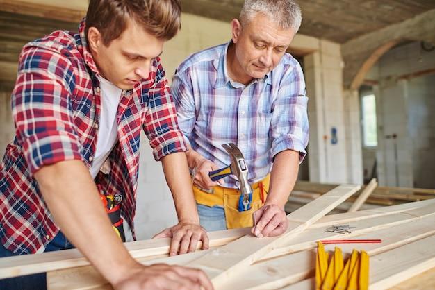 Cerca de carpinteros con martillo golpeando tablones