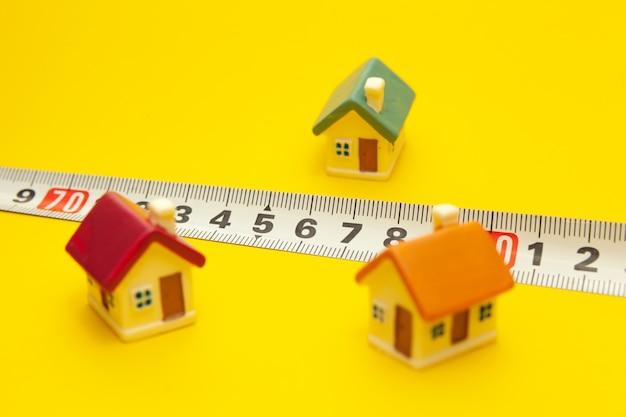 De cerca. casas de colores en miniatura sobre un fondo amarillo con una cinta métrica