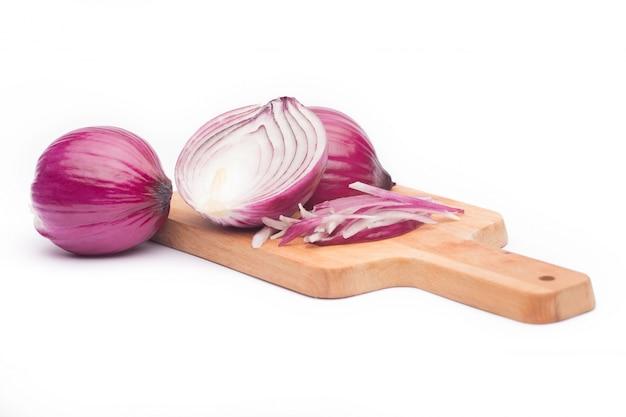 Cerca de la cebolla roja rebanada y de la cebolla roja entera en una tabla de madera.