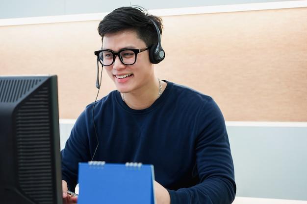 De cerca en el centro de llamadas hombre con el equipo que trabaja hablando en los auriculares