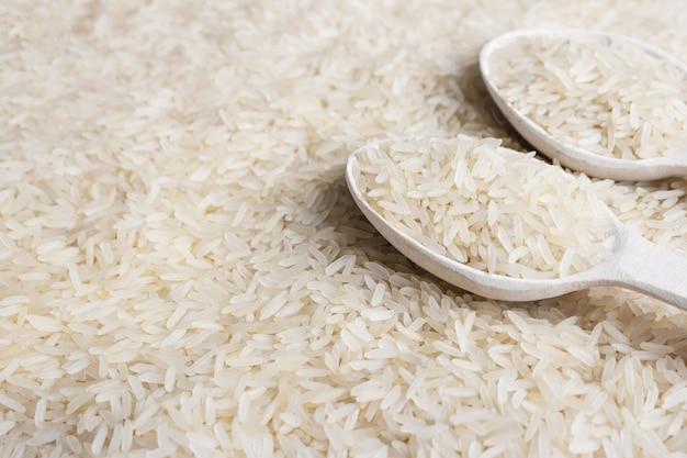 Cerca de cereal de arroz blanco y cuchara de madera