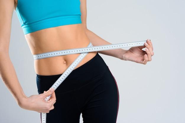 De cerca. chica mide la cintura con centímetro.