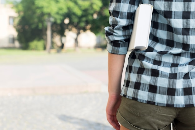 Cerca de la chica de secundaria sosteniendo el libro bajo el brazo