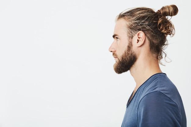 Cerca de chico guapo hipster barbudo con pelo en moño