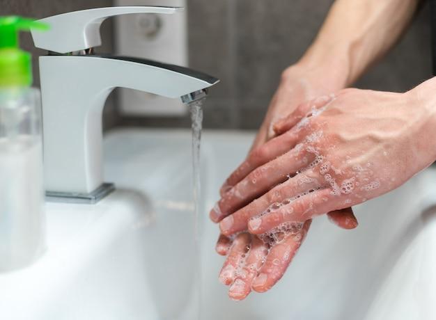 De cerca. chico moderno enjabonándose cuidadosamente las manos. concepto de prevención de enfermedades infecciosas.