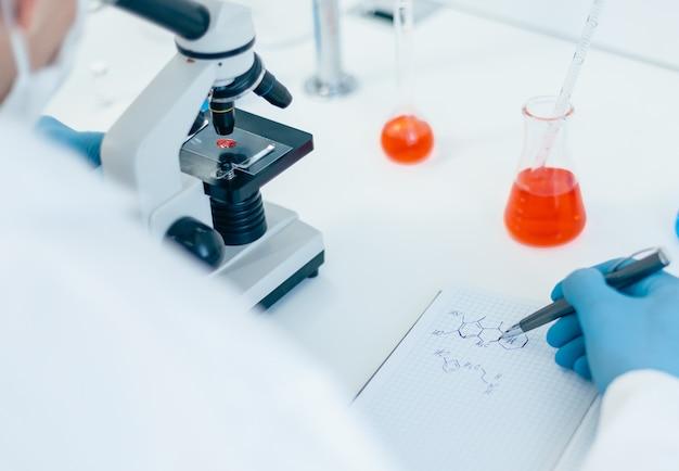 De cerca. científico mirando una gota de sangre a través de un microscopio. foto con espacio de copia.