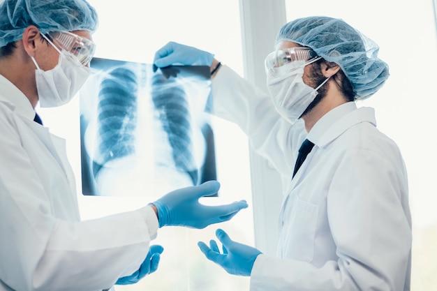 De cerca. científicos con máscaras protectoras mirando una radiografía de los pulmones.