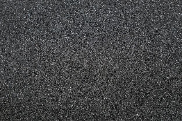 Cerca de la cinta de agarre del monopatín, fotografía macro de textura de papel de lija.
