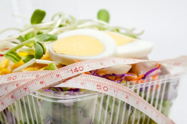 Cerca de la cinta métrica con huevo de pollo y verduras frescas de ensalada