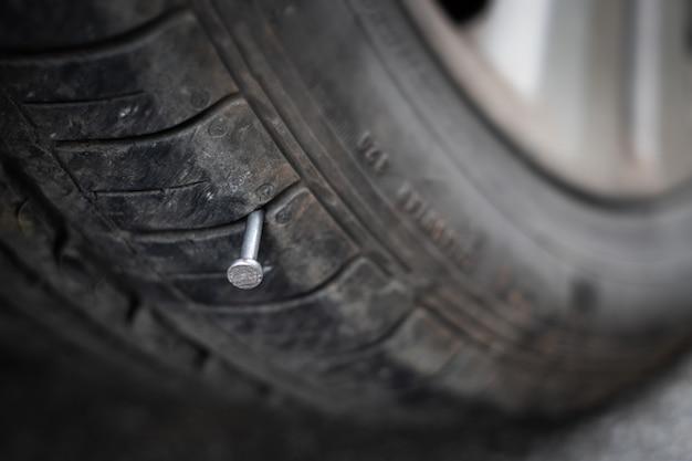Cerca de clavo de metal pegado en el neumático de la rueda