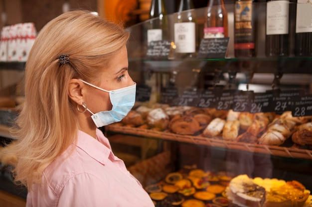 Cerca de una clienta con mascarilla médica, comprando pasteles en la panadería