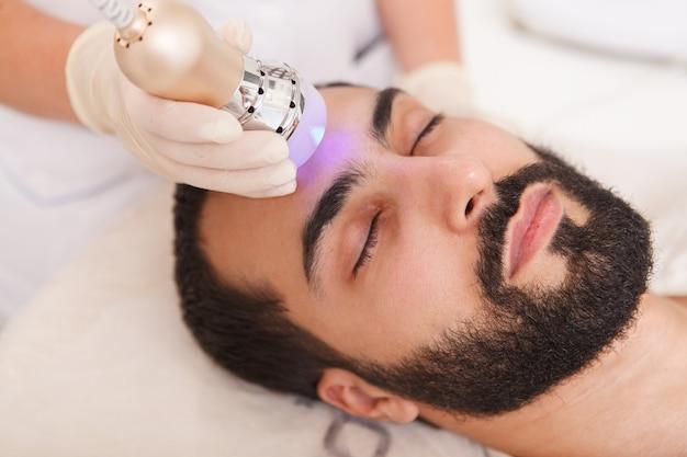 Cerca de un cliente masculino que disfruta de un tratamiento de lifting facial anti-envejecimiento por esteticista
