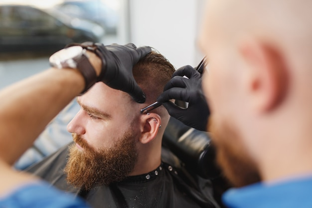 Cerca del cliente de servicio de peluquería profesional masculina, afeitado de barba grande y gruesa con navaja recta