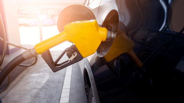 Cerca del coche está rellenando combustible combustible en la estación de servicio