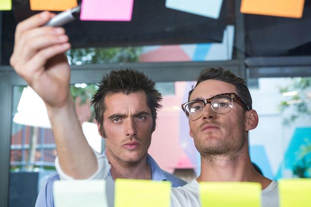 Cerca de colegas mirando notas adhesivas