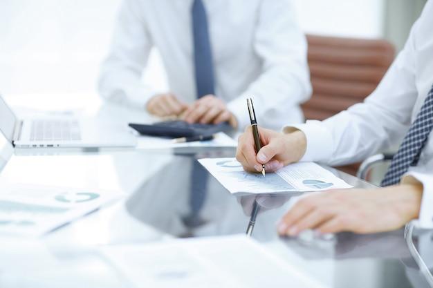Cerca de colegas de negocios que compilan el informe financiero