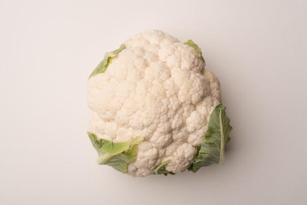 Cerca de una coliflor madura aislada sobre blanco