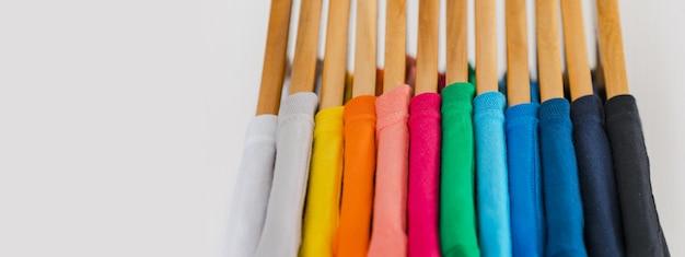 Cerca de coloridas camisetas en perchas