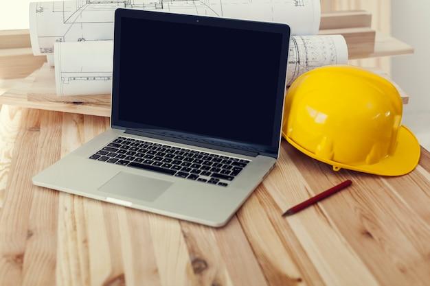 Cerca de la computadora portátil en el lugar de trabajo para el trabajador de la construcción