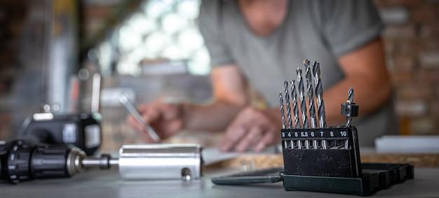 Cerca de un conjunto de taladros para madera sobre una mesa de trabajo de un carpintero en un taller.