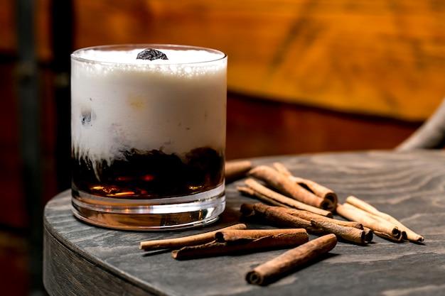 Cerca de una copa de cóctel cremoso marrón junto a los palitos de canela
