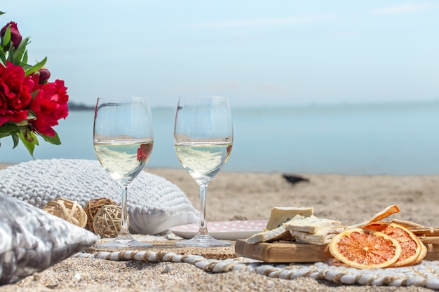 Cerca de copas de champán y bocadillos a la orilla del mar. concepto de vacaciones y romance.