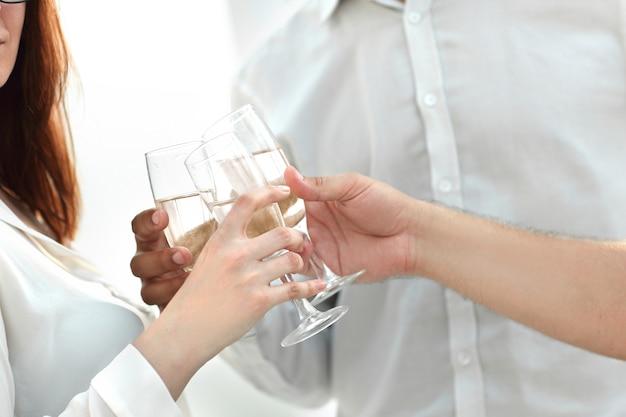 De cerca. copas de vino en manos del equipo empresarial. el concepto de una startup exitosa