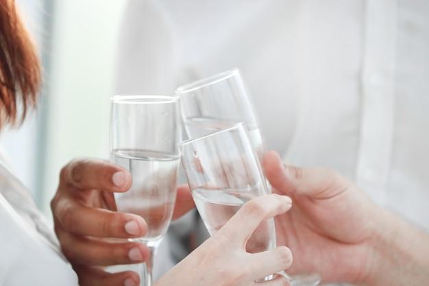 De cerca. copas de vino en manos de socios comerciales. concepto de éxito