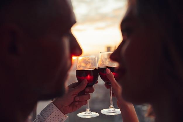 Cerca de copas con vino sosteniendo por amantes