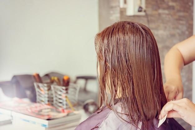 Cerca del corte de pelo de la mujer en el fondo borroso salón de pelo