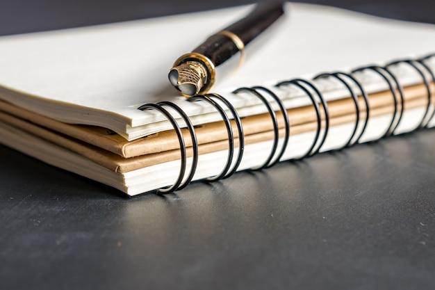 Cerca del cuaderno kraft vacío y lápiz negro sobre negro