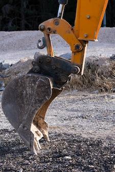 Cerca del cucharón de la excavadora. piezas de maquinaria de excavación, detalle de la industria de la pala excavadora. dientes de la cuchara sucia excavadora amarilla de construcción. cuchara de excavadora descansando en el sitio de construcción
