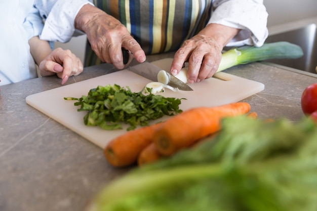 Cerca de una dama senior cortar verduras en un tablero