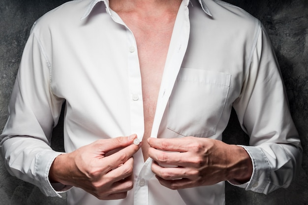 Cerca de un hombre quitándose la camisa blanca sobre fondo gris grunge