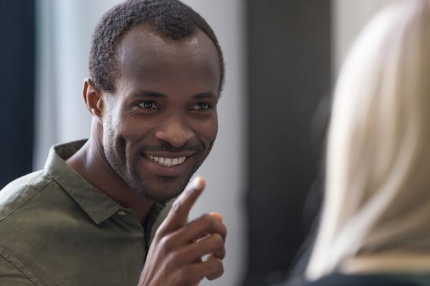 Cerca de un dedo acusador sonriente joven africano