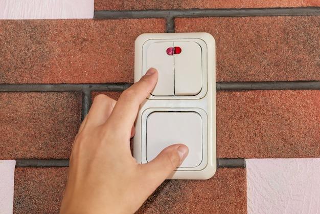 Cerca del dedo femenino se apaga el interruptor de iluminación en casa. poder, energía, ahorro eléctrico, copie el espacio.