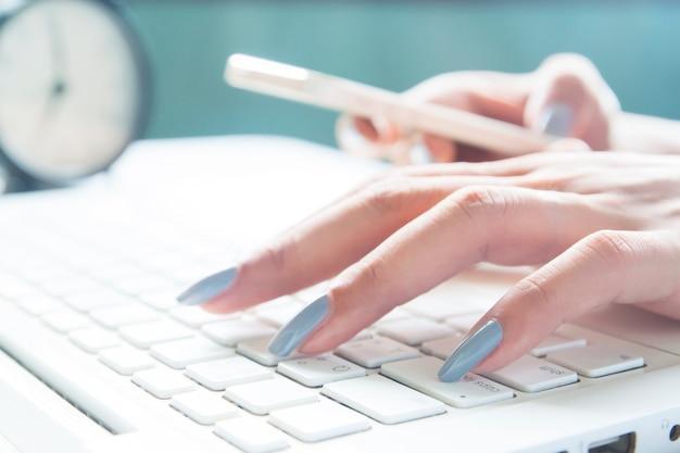 Cerca de los dedos femeninos utilizando equipo portátil y móvil, mujer trabajadora y concepto de compras en línea