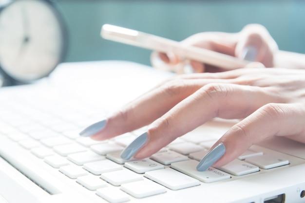 Cerca de los dedos femeninos utilizando equipo portátil y móvil, mujer trabajadora y el concepto de compras en línea