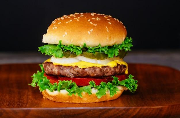 Cerca de deliciosa hamburguesa fresca o tablero de madera