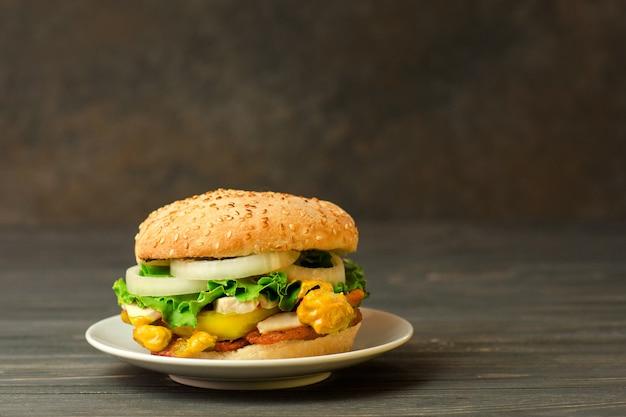 Cerca de deliciosa hamburguesa con sésamo. deliciosa hamburguesa casera en la mesa de madera. espacio libre para texto