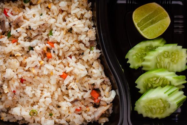 Cerca de delicioso arroz frito con pepino y limón en lado en fiambrera