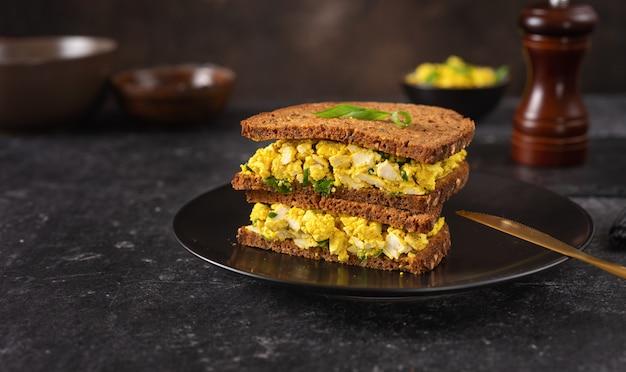 Cerca de delicioso y colorido sandwich de hamburguesa vegana con ensalada de huevo vegano