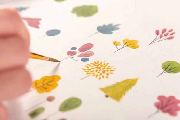 Cerca de diferentes flores coloridas diseño de la naturaleza pintadas con pincel y acuarelas sobre papel