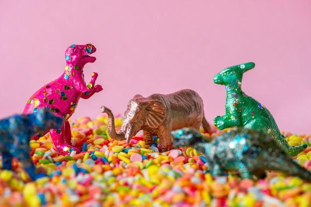 Cerca de dinosaurios y juguetes de figuras de animales en dulces confites
